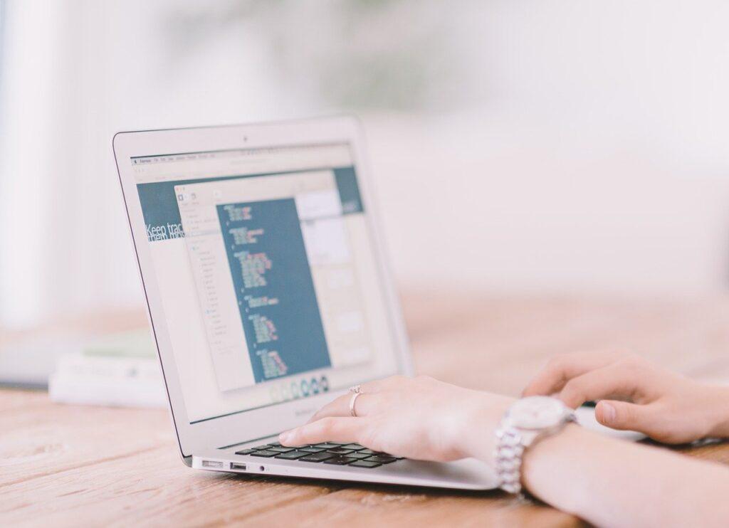 パソコンのキーボードを叩く女性画像